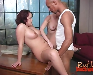 Bald-headed guy fucks two spunky bitches on the couch